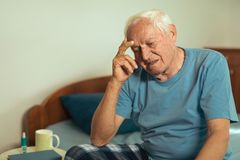 Senior man suffering from depression. Senior man sitting on bed at home suffering from depression Royalty Free Stock Photography