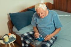 Senior Man Sitting On Bed Taking Medication Stock Image