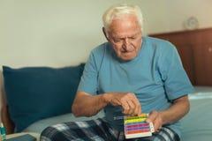 Senior Man Sitting On Bed Taking Medication Royalty Free Stock Image