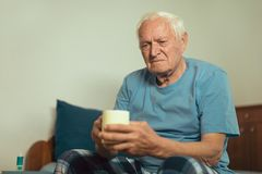 Senior Man Sitting On Bed With Hot Drink stock photos