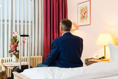 Senior man sitting on the bed in the hotel room Stock Photos