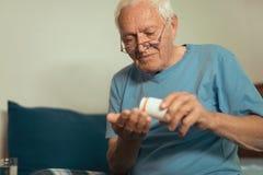 Senior Man Sitting On Bed Taking Medication Royalty Free Stock Images