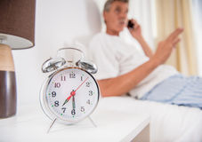 Senior man. Is sitting in bed and talking by phone. Focus on alarm clock Stock Photos
