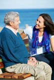 Senior Man Sitting On Bench With Daughter. Senior Man Sitting On Bench With Adult Daughter By Sea Royalty Free Stock Photos