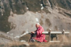 Senior man is sitting on the bench in the mountain royalty free stock images