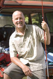Senior man sitting in boot of parked SUV, holding fishing rod, smiling, portrait Royalty Free Stock Photo