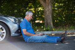 Senior man sitting by car on road Stock Photography