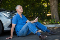 Senior man sitting by car on road after breakdown Stock Photo