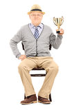 Senior man sitting on chair and holding trophy Royalty Free Stock Photography