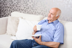 Senior man sitting on couch with cup Stock Photo