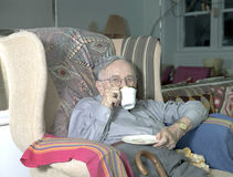 Senior man sitting on couch with cup drinking Stock Photo