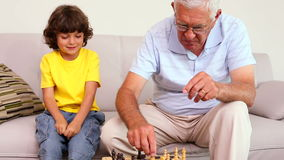 Senior man sitting on couch with his grandson playing chess