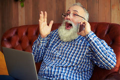 Senior man sitting on the couch with laptop Royalty Free Stock Images