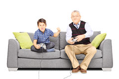 Senior man sitting on a couch and playing video games with his n Stock Images