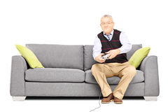 Senior man sitting on a couch and playing video games Royalty Free Stock Photos