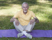Senior man sitting cross-legged on mat Royalty Free Stock Photos