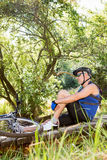 Senior man is sitting down beside his bike in a forest Stock Images