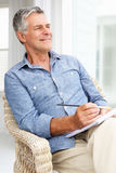 Senior man sitting down sketching Stock Photos