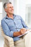 Senior man sitting down sketching. Looking off camera Stock Photos