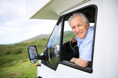 Senior man sitting at driving wheel Stock Image