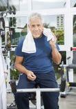 Senior Man Sitting On Exercise Bike At Rehab Fitness Center Royalty Free Stock Image