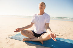Senior man sitting on exercise mat while meditating at beach Royalty Free Stock Photo