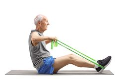Senior man sitting and exercising with an elastic band. Full length profile shot of a senior man sitting and exercising with an elastic band isolated on white royalty free stock image