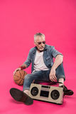 Senior man sitting on floor with tape recorder and basketball ball Stock Images