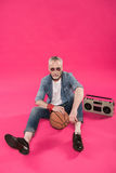 Senior man sitting on floor with tape recorder and basketball ball Royalty Free Stock Photography