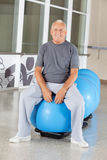 Senior man sitting on gym ball Stock Photos