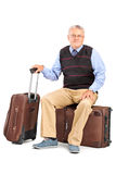 Senior man sitting on his baggage Stock Photo