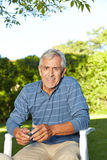Senior man sitting in his garden Royalty Free Stock Photos