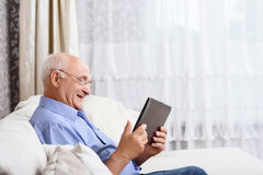 Senior man  sitting and holding tablet Royalty Free Stock Images