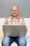 Senior man sitting with laptop at home Stock Image