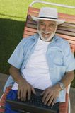 Senior Man sitting on Lawn Chair Using Laptop elevated view portrait. Royalty Free Stock Image