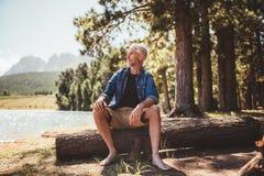 Senior man sitting on log and looking at the lake. Portrait of senior man sitting on a wooden log and looking at the lake. Mature man camping by a lake Stock Photo