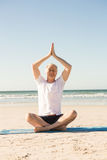 Senior man sitting on mat while meditating at beach Royalty Free Stock Photo