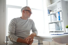 Senior man sitting at medical office table Stock Images