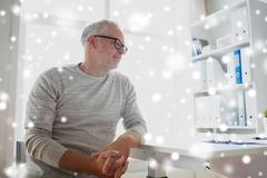Senior man sitting at medical office table. Old age, problem, healthcare and people concept - sad senior man sitting at table at medical office over snow Stock Photo