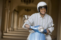 Senior man sitting on motor scooter near colonnade, smiling, front view (tilt) Stock Photo