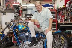 Senior man sitting on motorcycle in workshop Royalty Free Stock Image
