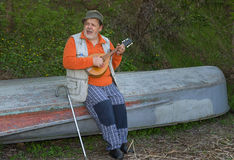 Senior man sitting on an old reversed boat and singing. Playing himself with mandolin royalty free stock image