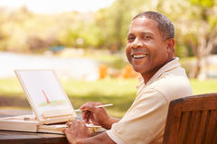 Senior Man Sitting At Outdoor Table Painting Landscape Stock Images