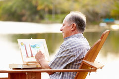Senior Man Sitting At Outdoor Table Painting Landscape Stock Photos