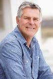 Senior man sitting outdoors. Smiling at camera royalty free stock image