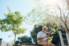 Senior man sitting outdoors and using cell phone Stock Photo