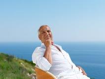 Senior man sitting outside Stock Image
