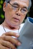 Senior man sitting outside reading a book Stock Image