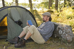 Senior man sitting outside a tent reading a book Stock Photo