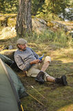 Senior man sitting outside a tent reading a book Stock Image